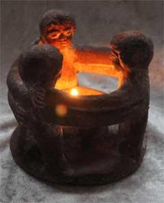 Drei Figuren Hand in Hand im Kreis um ein Feuer