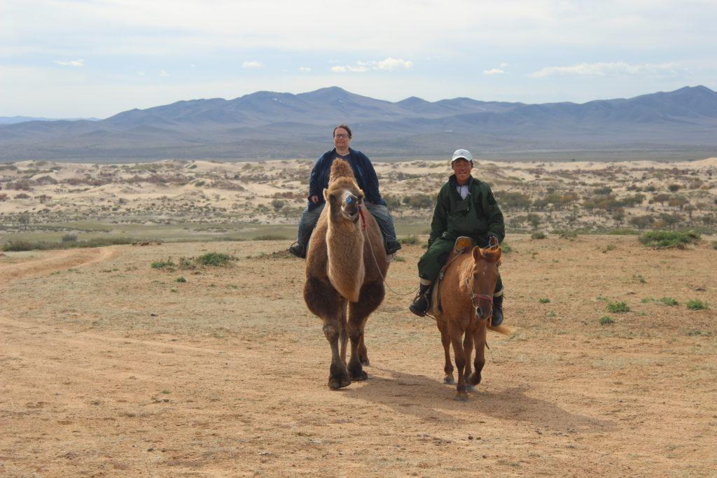Die Erzählerin hoch zu Kamel in einer mongolischen Steppenlandschaft