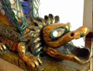 Ein Drache mit aufgerissenem Maul, großen Augen, Löwenmähne, Vordertatzen und  Flügel des Künstlers Tamahara