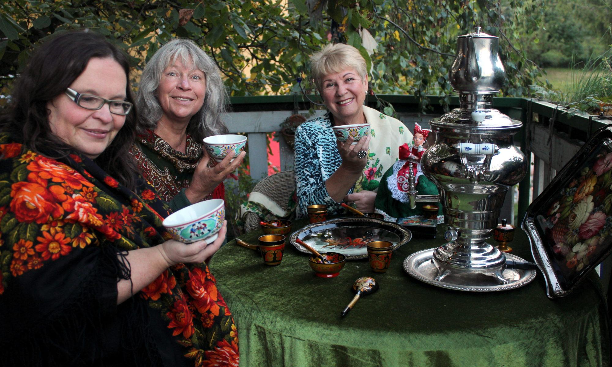 Drei Frauen beim Teetrinken. Auf dem Tisch steht ein Samowar.