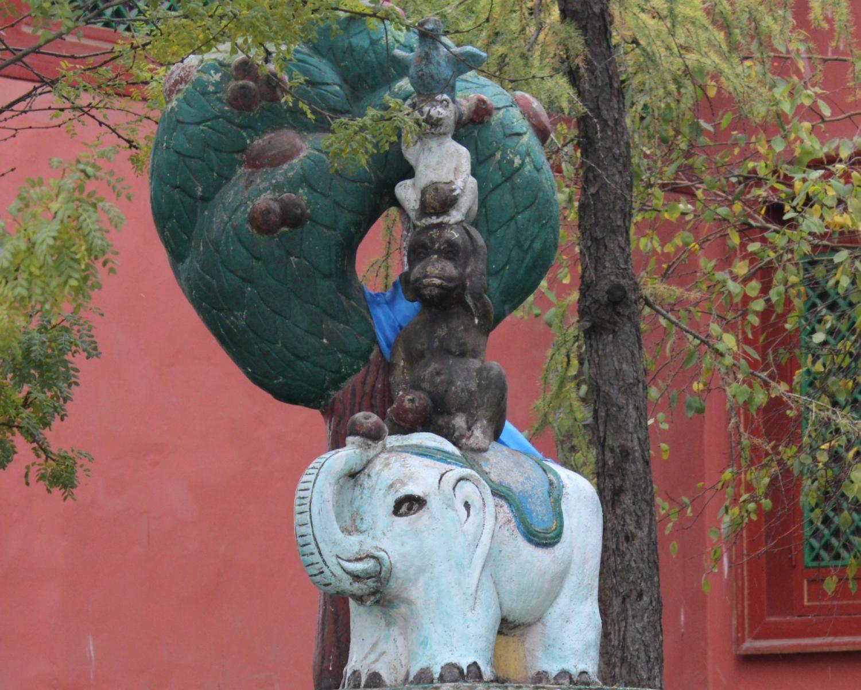 Die Statue von einem Elefanten, einem Affen, einen Hasen und einer Taube, die übereinander und unter einem Baum stehen