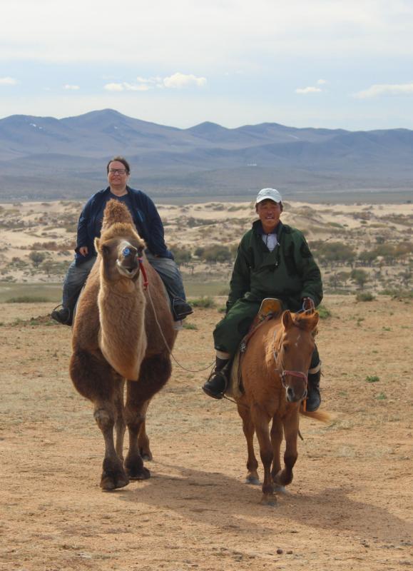 Die Erzählerin hoch zu Kamel in einer mongolischen Gebirgswüstenlandschaft