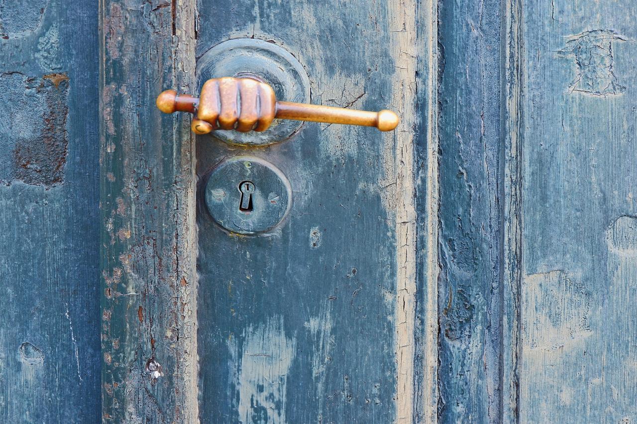 Türgriff in Form einer Hand auf blauer verwitterter Holztür